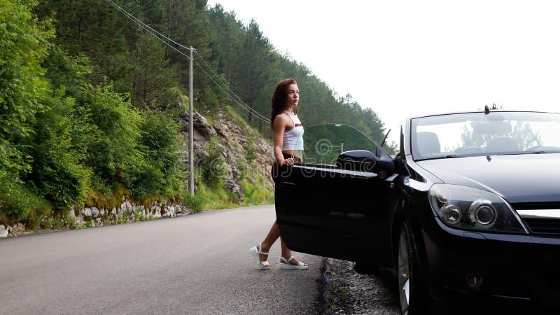 Seksowna brunetka trzyma otwarte drzwi czarny kabriolet Ubierający w krótkich czerwonych skrótach i białej koszulce obraz royalty free