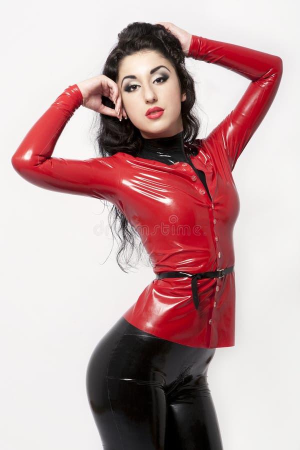 Seksowna brunetka w czarnym i czerwonym lateksie zdjęcia royalty free