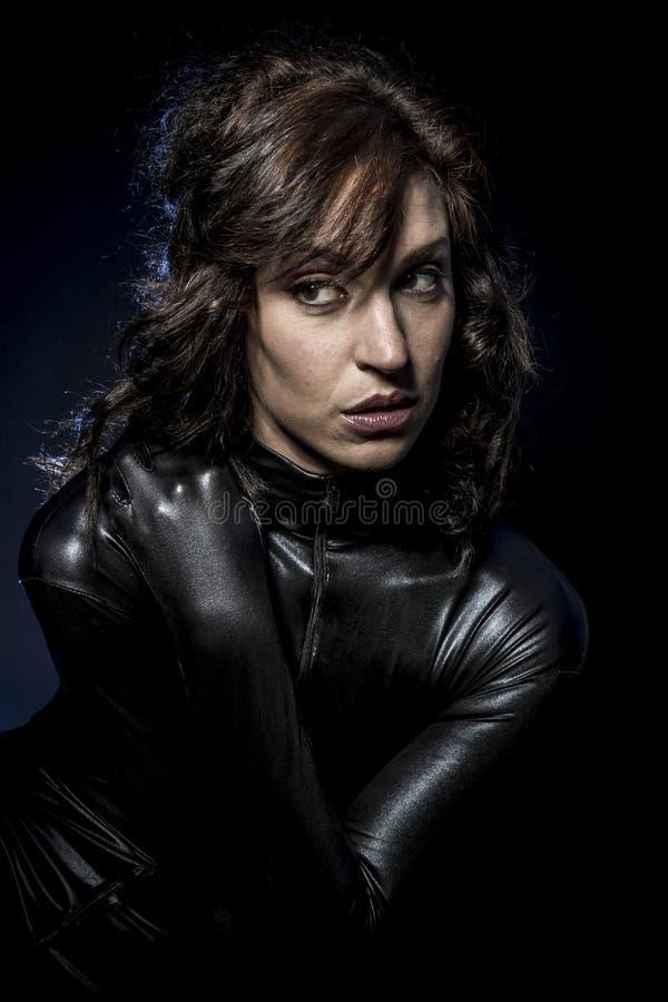 Seksowna brunetka w czarnym lateksowym kostiumu, moda strzelał kobieta wewnątrz zdjęcia royalty free