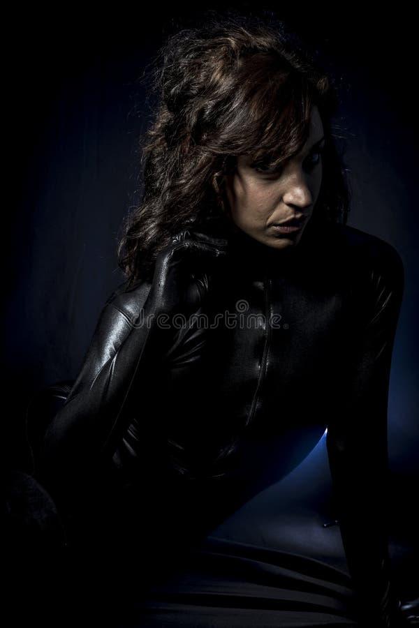 Seksowna brunetka w czarnym lateksowym kostiumu, moda strzelał kobieta wewnątrz obraz stock