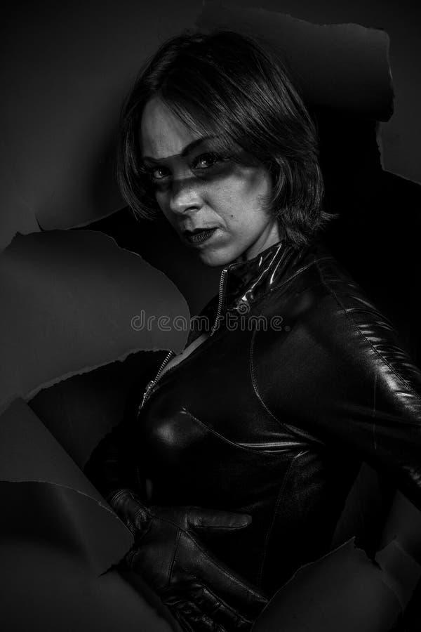 Seksowna brunetki dziewczyna ubierał w czarnym lateksowym kombinezonie zdjęcia stock