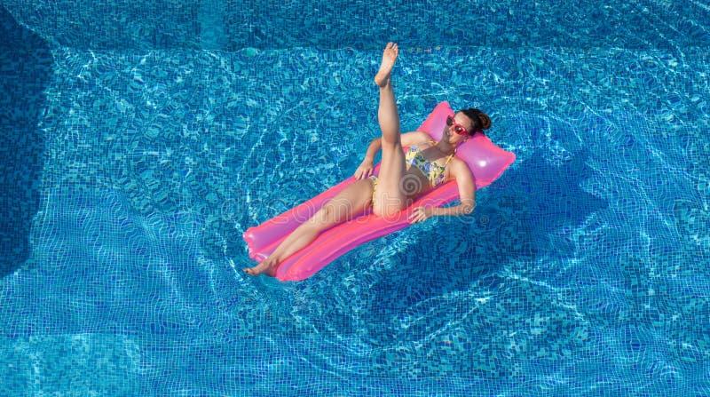 Seksowna brunetki kobieta robi gimnastycznemu ćwiczeniu na nadmuchiwanym mattr obrazy stock
