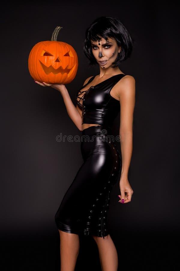 Seksowna brunetki kobieta w Halloweenowym makeup i bielizna trzymamy bani na czarnym tle w studiu Makijażu kościec, potwór fotografia stock