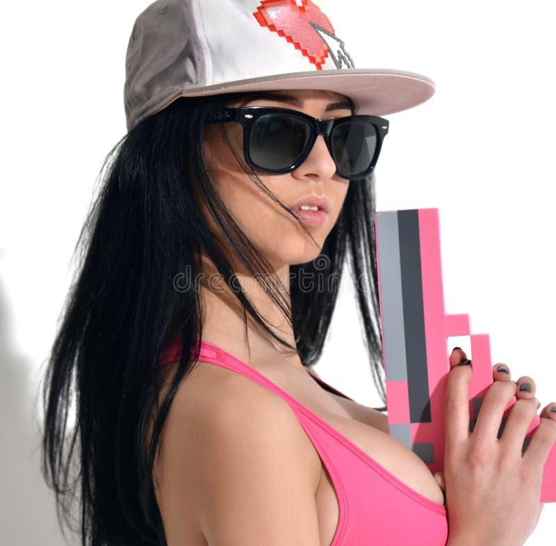 Seksowna brunetki kobieta w nakrętce z różową piksla pistoletu zabawką i sunglass obrazy stock