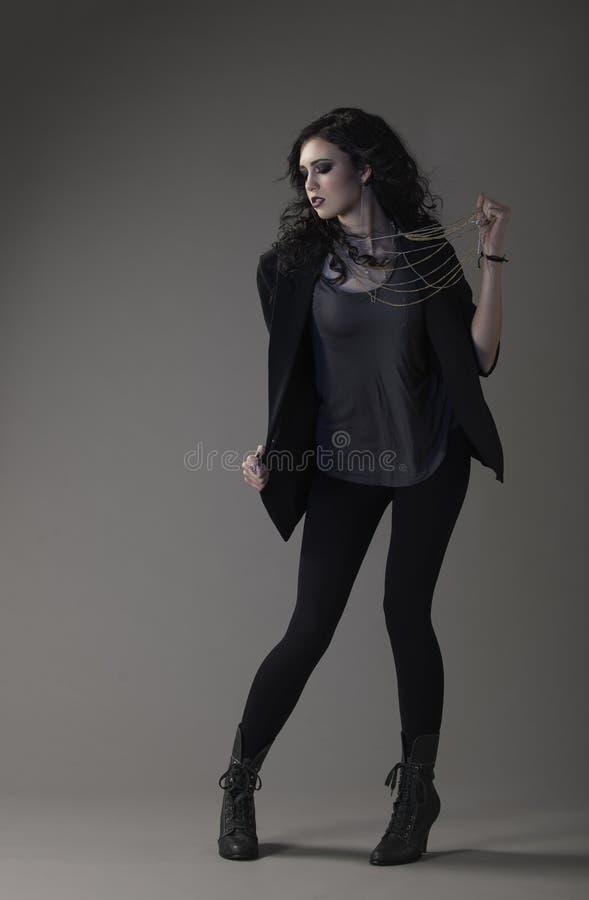 Seksowna brunetki kobieta w zirytowanym ciemnym stroju obraz royalty free