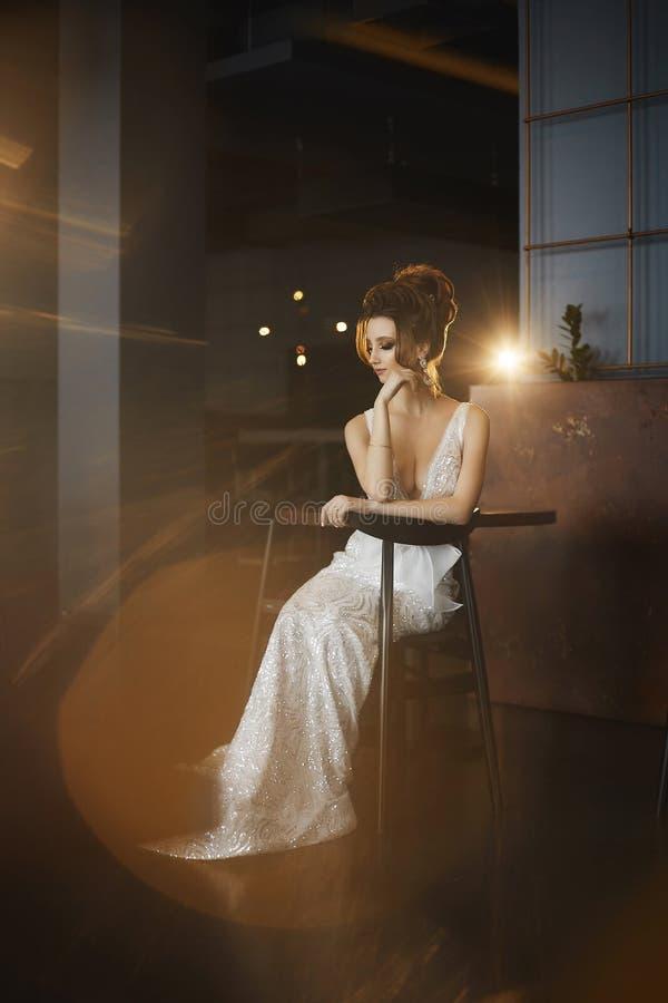 Seksowna, busty i piękna brunetka modela dziewczyna z, siedzi na krześle i pozować wewnątrz fotografia stock