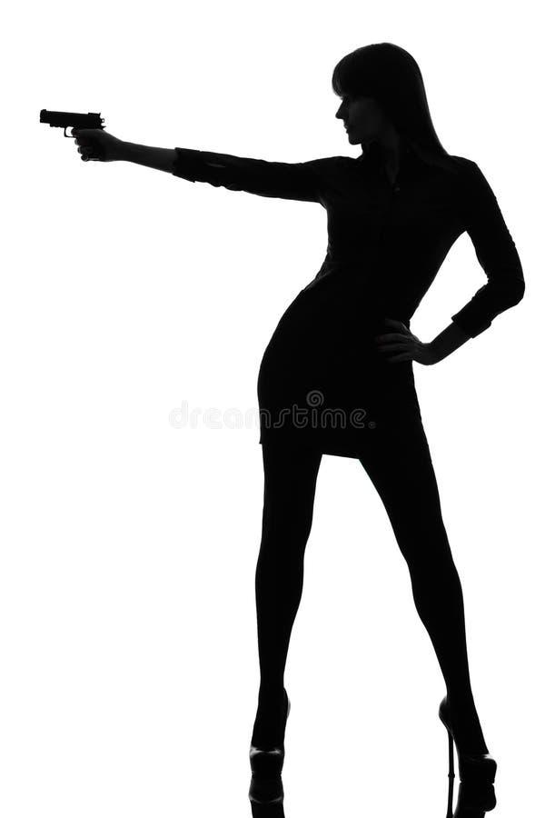 Seksowna detektywistyczna kobiety mienia celowania pistoletu sylwetka fotografia royalty free