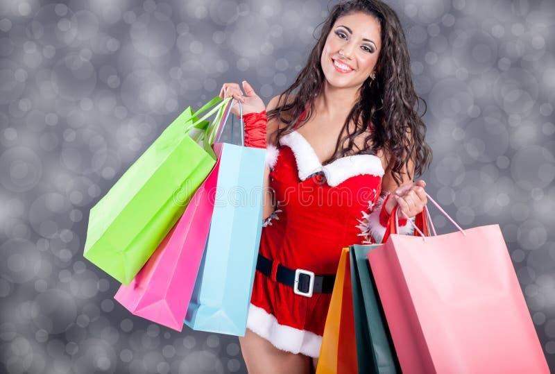 Seksowna dziewczyna jest ubranym Santa Claus odziewa z kolor torbą zdjęcie stock