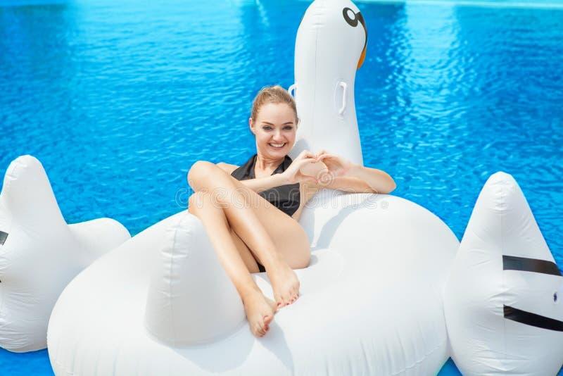 Seksowna dziewczyna w czarnym pływackiego kostiumu lying on the beach na nadmuchiwanych mattres zdjęcie royalty free