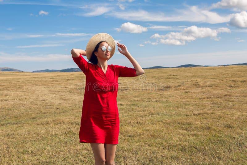 Seksowna dziewczyna w czerwieni sukni pozyci w polu w jesieni fotografia stock
