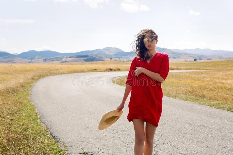 Seksowna dziewczyna w czerwieni sukni pozyci w polu w jesieni obraz royalty free