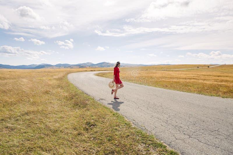Seksowna dziewczyna w czerwieni sukni pozyci w polu w jesieni zdjęcie stock