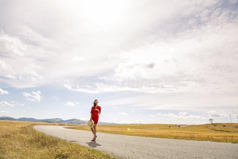 Seksowna dziewczyna w czerwieni sukni pozyci w polu w jesieni zdjęcia royalty free