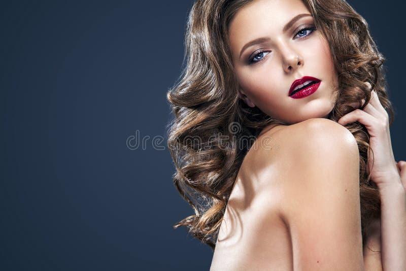 Seksowna dziewczyna z falistym włosy i ładnym makeup długim, błyszczącym, Piękny model, kędzierzawa fryzura na błękitnym tle fotografia royalty free