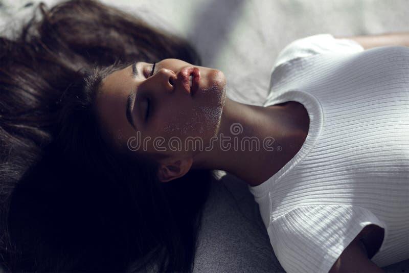 Seksowna garbnikująca brunetki dziewczyna z zamkniętymi oczami i dużymi zmysłowymi wargami kłama na plaży na białym piasku z cien zdjęcia stock