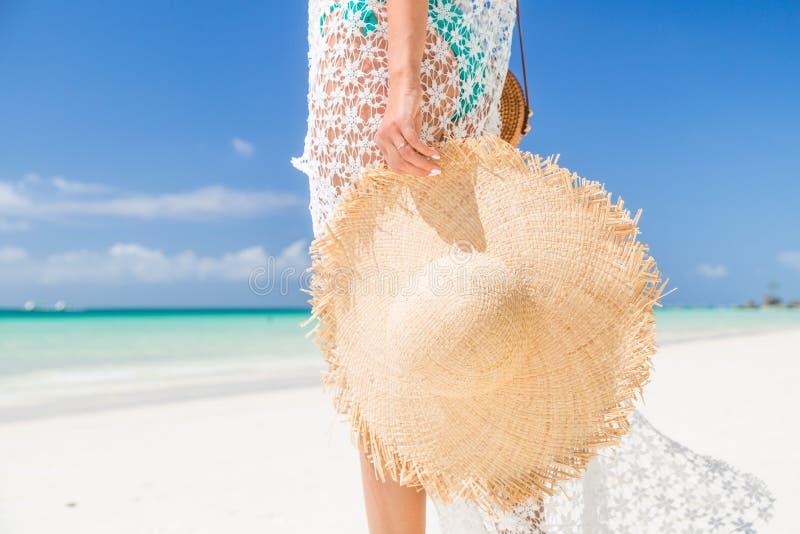 Seksowna garbnikuj?ca dziewczyna trzyma du?ego s?omianego kapelusz na seashore w b??kitnym bikini i bia?ym tunica Poj?cie wakacje zdjęcie stock