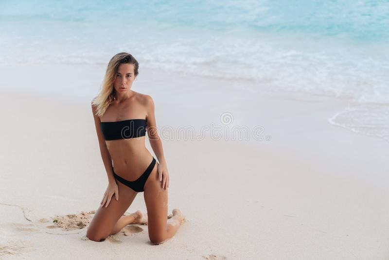 Seksowna garbnikująca dziewczyna w czarnym swimsuit pozuje na piaskowatej plaży zdjęcia royalty free