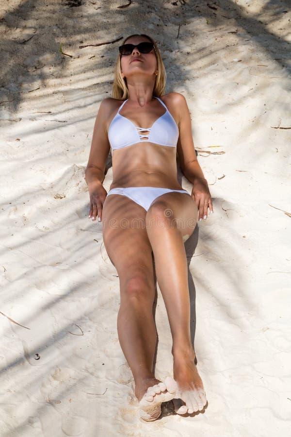 Seksowna garbnikuj?ca dziewczyna w bia?ym swimsuit pozuje na piaskowatej pla?y Pi?kny model sunbathes i odpoczywa na oceanu brzeg zdjęcia royalty free