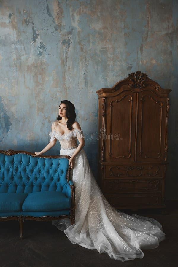 Seksowna i piękna brunetka modela dziewczyna w koronki sukni z nagimi ramionami opiera na zdjęcia stock