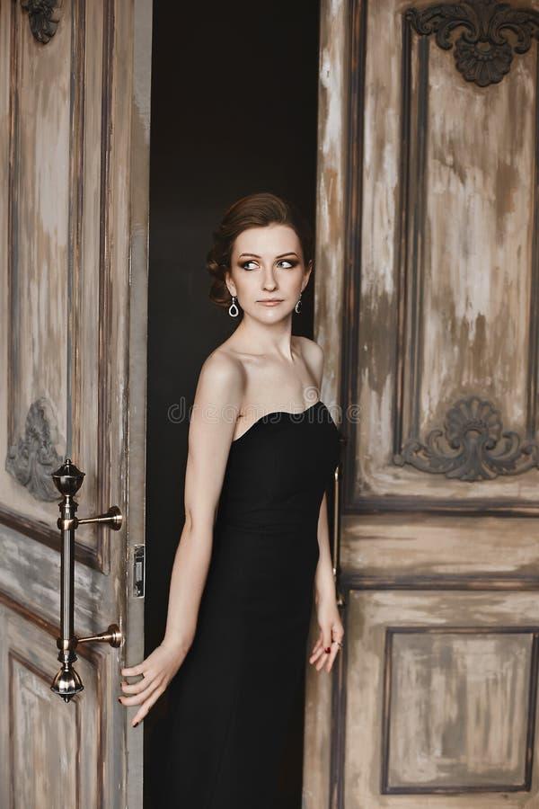 Seksowna i piękna brunetka modela dziewczyna z modnym ostrzyżeniem z jaskrawym makeup w modnej czarnej ciasnej sukni i, zdjęcie stock