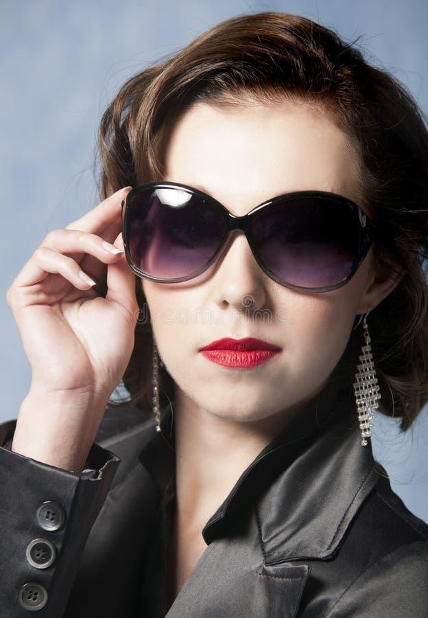 Seksowna kobieta pozuje z okularami przeciwsłonecznymi, czerwoną pomadką i kurtką, fotografia stock