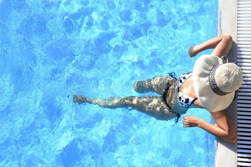 Seksowna kobieta relaksuje w basenie w bikini i sunhat obraz stock