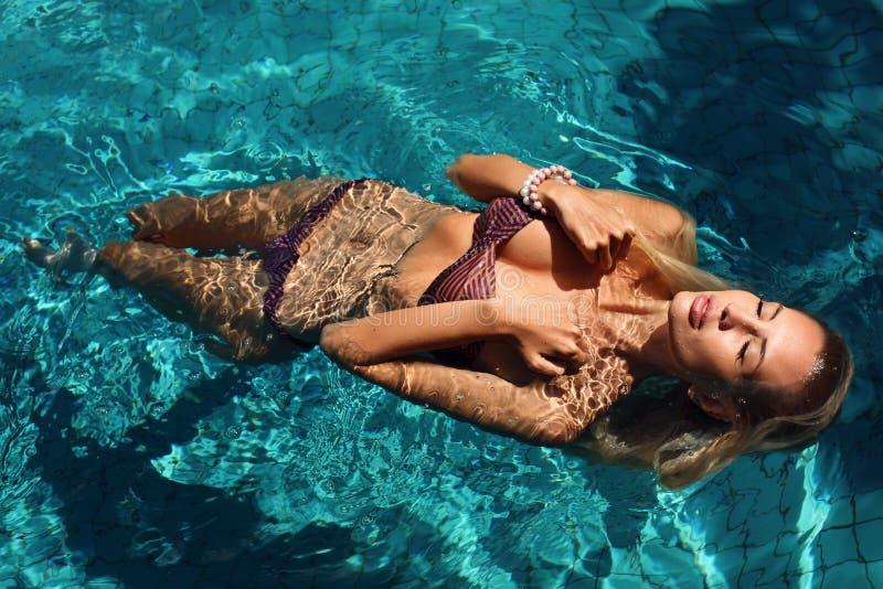 Seksowna kobieta relaksuje w pływackim basenie z blondynem w bikini obrazy royalty free