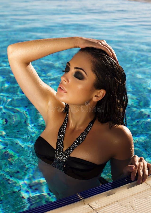 Seksowna kobieta relaksuje w pływackim basenie z długie włosy w bikini zdjęcia royalty free