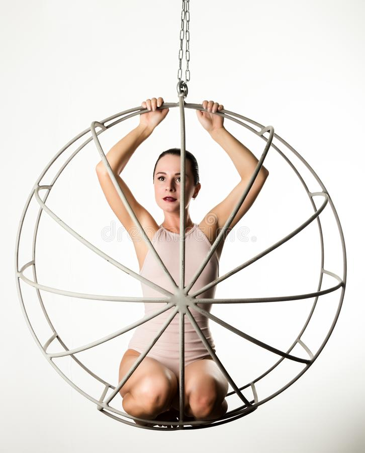 Seksowna kobieta w beżowym swimsuit na metal klatce na białym tle fotografia royalty free