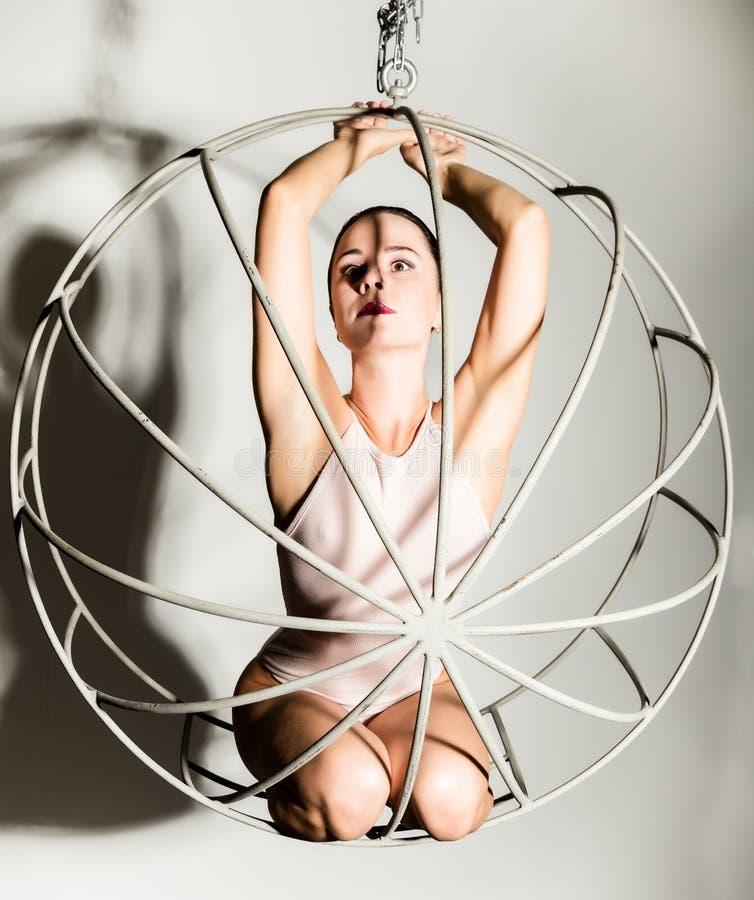 Seksowna kobieta w beżowym swimsuit na metal klatce na białym tle zdjęcia stock