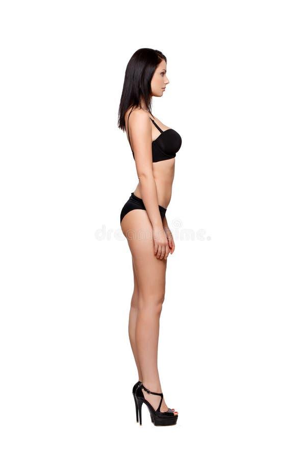 Seksowna kobieta w bikini pozuje bocznego widok fotografia royalty free