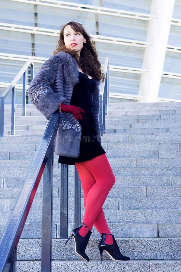 Seksowna kobieta w czarnej sukni, czerwonych rajstopy i futerkowym żakiecie, obraz stock