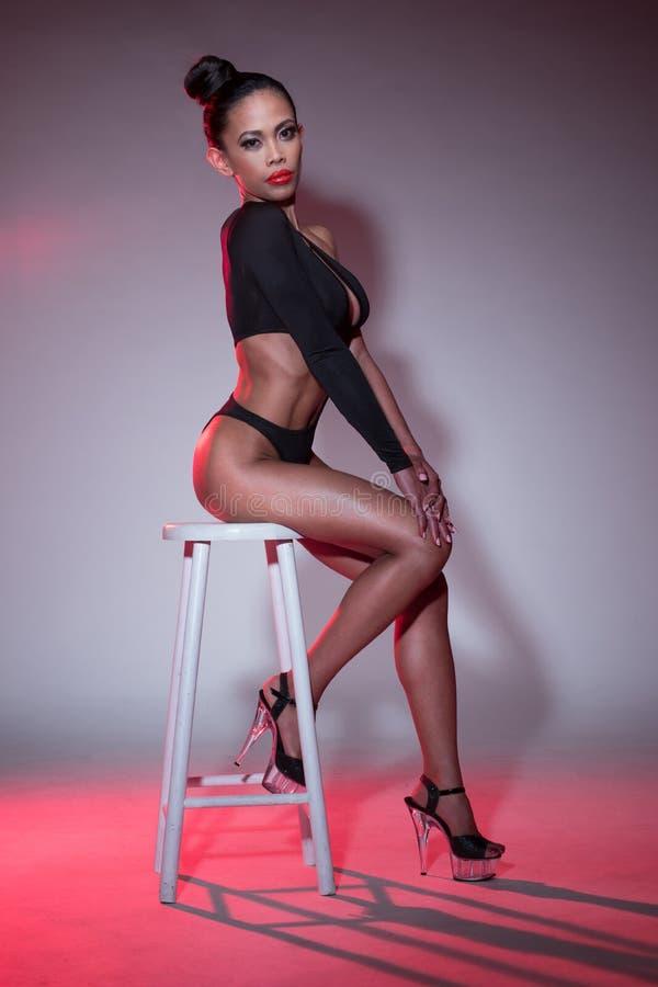 Seksowna kobieta w Czarnym Leotard obsiadaniu na stolec fotografia stock