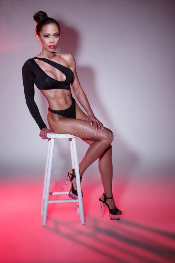 Seksowna kobieta w Czarnym Leotard obsiadaniu na stolec obraz stock