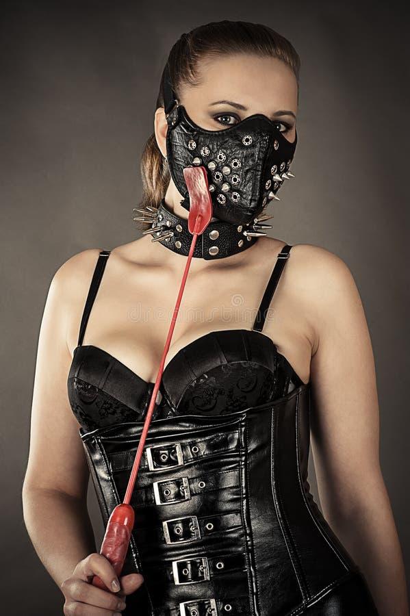 Seksowna kobieta w gorseciku i maska z kolcami fotografia stock