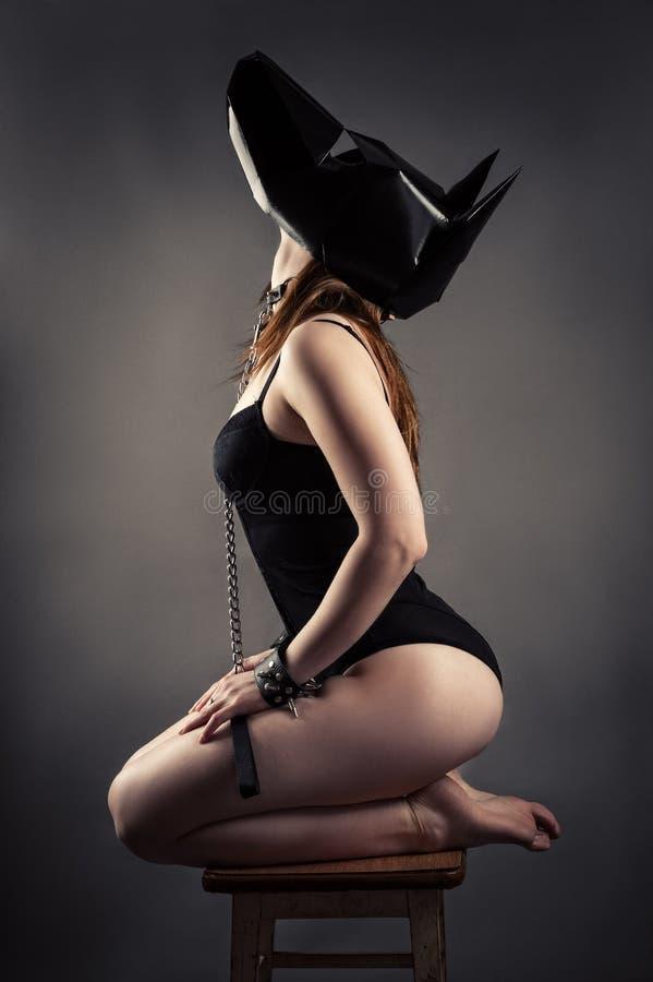 Seksowna kobieta w pies maski siedzącym klęczeniu na krześle i przyglądającym up zdjęcie stock