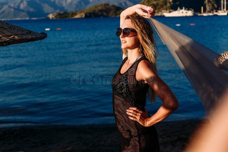 Seksowna kobieta w przejrzystej tunice w jaskrawym zmierzchu świetle na morzu zdjęcia royalty free