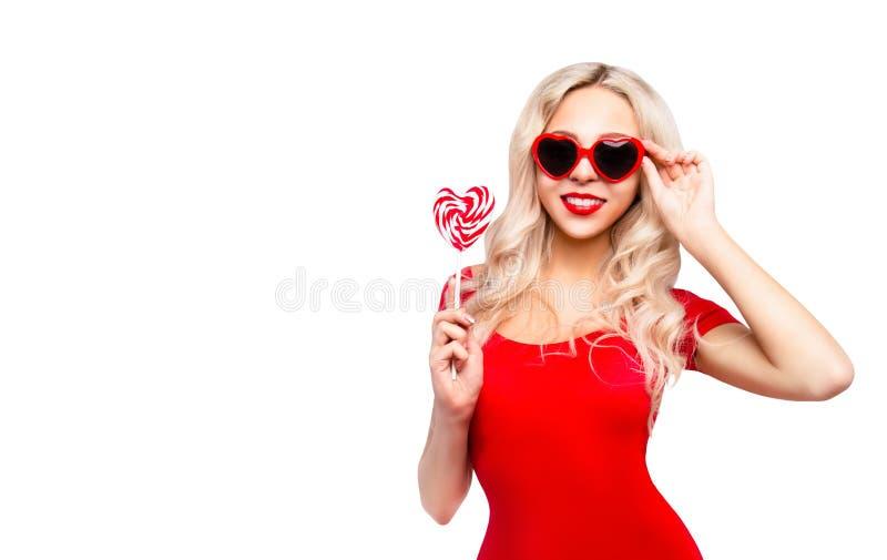 Seksowna kobieta z czerwonymi wargami w okularów przeciwsłonecznych sercach lizak w kształcie serca fotografia royalty free