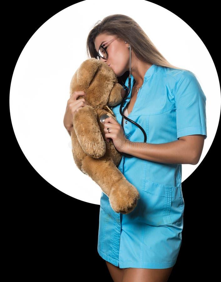 Seksowna kobiety lekarka z stetoskopem uzdrawia misia na białym okręgu czarnym tle i obraz stock
