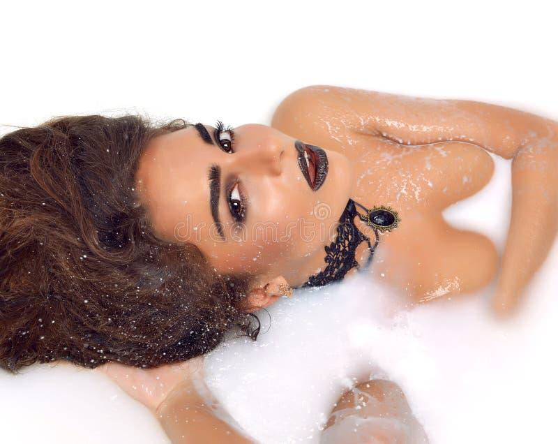 Seksowna kobiety twarz kłama ono uśmiecha się w bielu mleka skąpaniu z pluśnięciami c zdjęcia stock