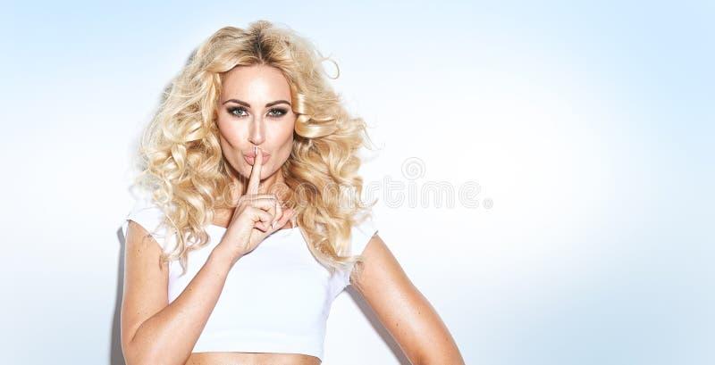 Seksowna młoda blondynki kobieta trzyma jej palec jej wargi w gest fotografia royalty free