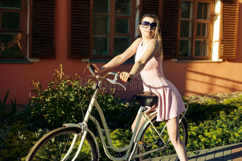 Seksowna młoda dziewczyna na bicyklu z szkieł i menchii suknią pozuje portreta obsiadanie na siedzeniu fotografia stock