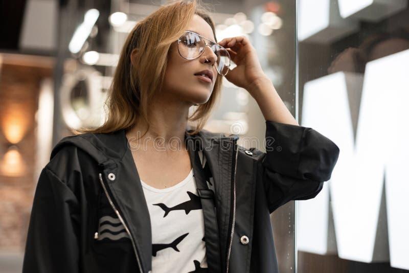 Seksowna młoda modniś kobieta w białej koszulce z wzorem w rocznik kurtce jest stojakami i prostuje modnych szkła fotografia stock