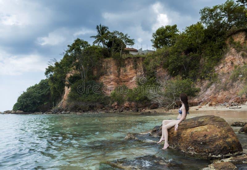 Seksowna młoda piękna kobieta w bikini obsiadaniu na skałach przy plażą zdjęcie royalty free