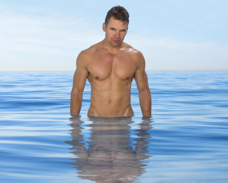Seksowna mięśniowa mężczyzna pozycja w oceanie zdjęcia royalty free