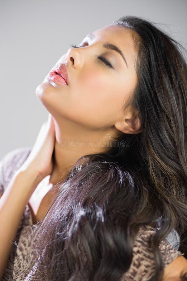 Seksowna piękna brunetka z zamkniętymi oczami dotyka szyję fotografia stock