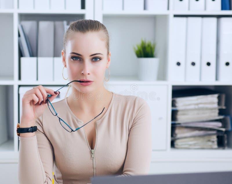 Seksowna sekretarka z szkłami w ręce rozbiera się w biurze, flircie i pragnieniu, Biurowa prowokacja zdjęcie royalty free