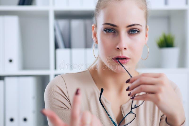 Seksowna sekretarka z szkłami w ręce rozbiera się w biurze, flircie i pragnieniu, Biurowa prowokacja obrazy stock