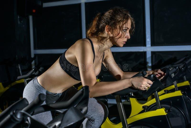 Seksowna sprawności fizycznej dziewczyna ćwiczy przy sprawności fizycznej gym przędzalnictwo zdjęcia stock