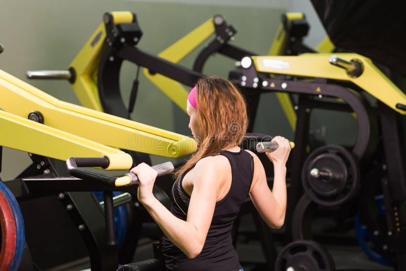 Seksowna sprawności fizycznej dziewczyna ćwiczy przy sprawności fizycznej gym Robi ćwiczeniu z sporta symulantem fotografia stock